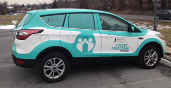 picture of suv with white and turquoise branding on exterior for Street Medicine
