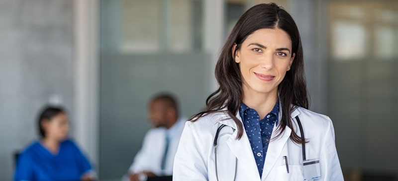 Female doctor smiling in white lab coat.