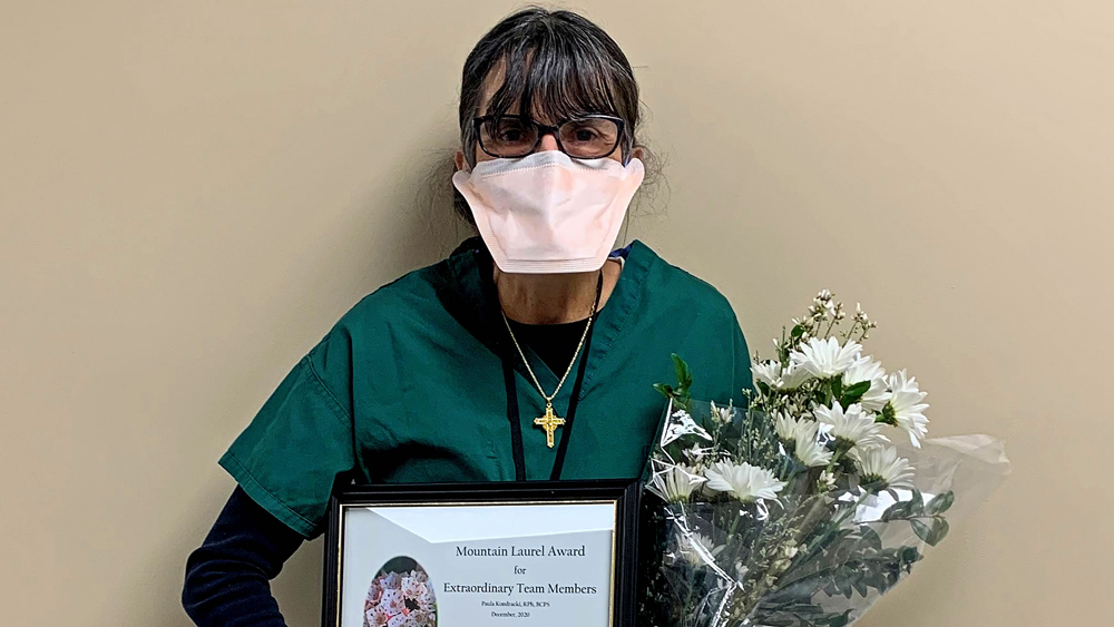 woman wearing a mask while holding a framed award