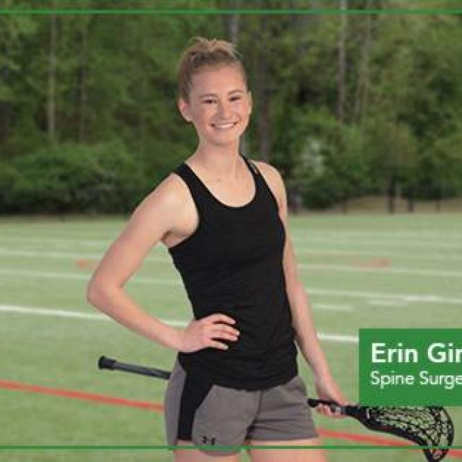 Girl with hand on her hip holding a lacrosse racket.