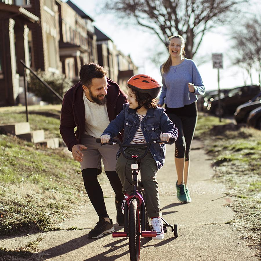 active parents help teach child to ride bike