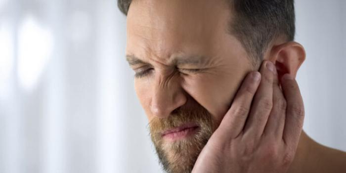 Man holding his ear in pain