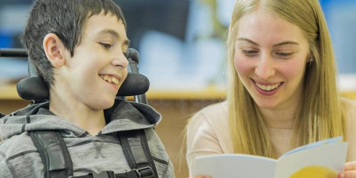 Volunteer reading to boy in wheelchair