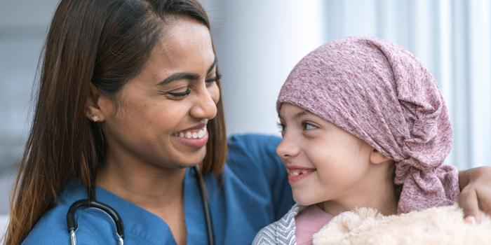 nurse smiling next to girl with cancer. Tower Health Pediatric Cancer Care