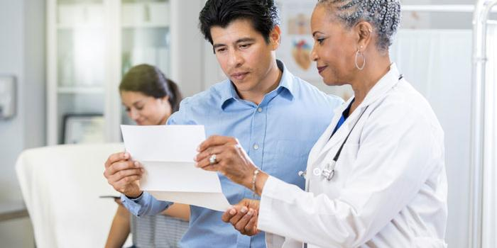 man holding paper next to doctor