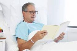 Man reading in hospital bed
