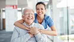 woman with arms around old man seated in hospital hallway